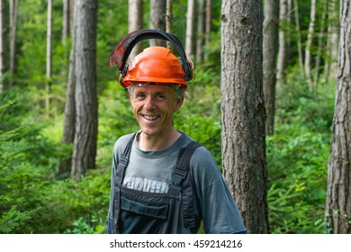 Lumberjack wearing protective helmet and earmuffs standing in the woods and smiling.