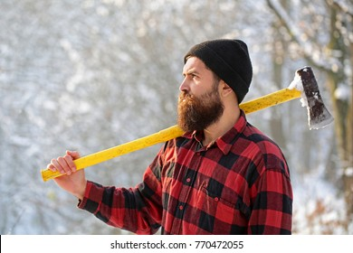 Lumberjack in the woods with an ax. Bearded man in hat with a hatchet. Handsome man, hipster. Lumberjack brutal bearded man with beard and moustache on winter day, snowy forest.