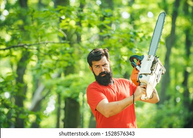 Lumberjack in the woods with chainsaw axe. Professional lumberjack holding chainsaw in the forest. Woodworkers lumberjack. Man doing mans job