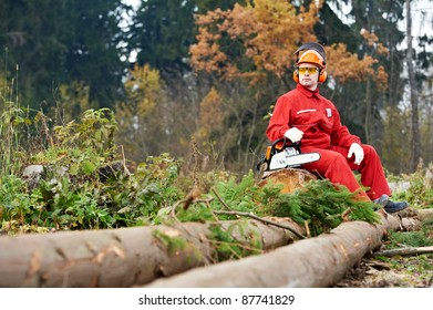 Lumberjack Worker With Chainsaw In The Forest. Resting