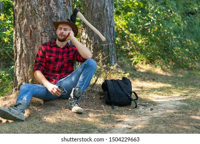 Lumberjack worker sitting in the forest. Lumberjack in the woods with an ax. Lumberjack with ax in his hands. Logging. Bearded man with axe concept. Lumberjack holding the axe