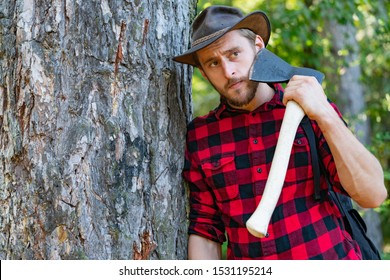 Lumberjack worker standing in the forest with axe. Lumberjack holding the axe. Strong man lumberjack with an ax in a plaid shirt. Lumberjack with ax in his hands