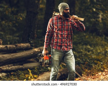Lumberjack worker standing  in the forest with axe and chainsaw