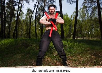 Lumberjack worker standing in the forest with axes. Strong healthy adult ripped man with big muscles standing with two big crossed axes outdoors