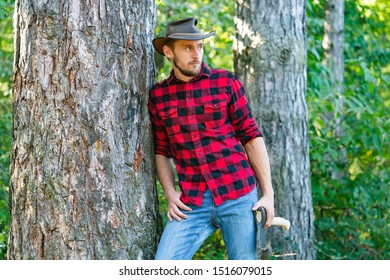 Lumberjack worker walking in the forest with axe. Lumberjack worker standing in the forest with axe. Lumberjack holding the axe. Lumberjack with axe on forest background