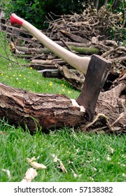 Lumberjack's axe stuck in a tree log on green grass with a pile of firewood in the background