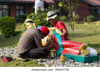 Lumbini, Nepal - November 26, 2014: Photograph of workers restorationg Buddha Statues at the Tara Foundation Lotus Stupa also known as German Temple.