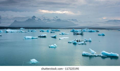 Luminous blue icebergs floating in Jokulsarlon glacial lagoon at dusk, Iceland