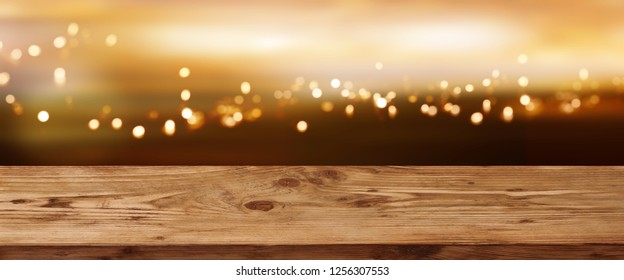 Luminous bokeh background in front of empty wooden table for festive decorations