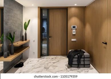 Luminous corridor with an entrance door in a modern interior with different walls and tiled floor. There is a lamp in a word form on textured gray wall, wooden racks with vases with plants, gray pouf.
