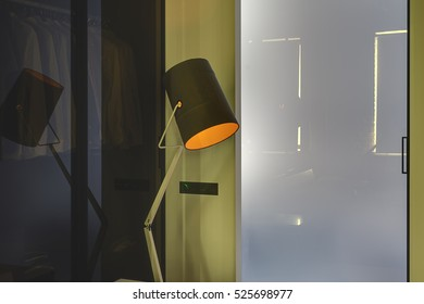 Luminous design lamp with the lampshade on the background of the light glassy frosted door in the modern interior with yellow walls. Behind the lamp there is a glass partition. Horizontal.