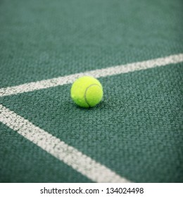 Luminous green high visibility tennis ball on a green tennis court lying in the angle of the lines forming the corner