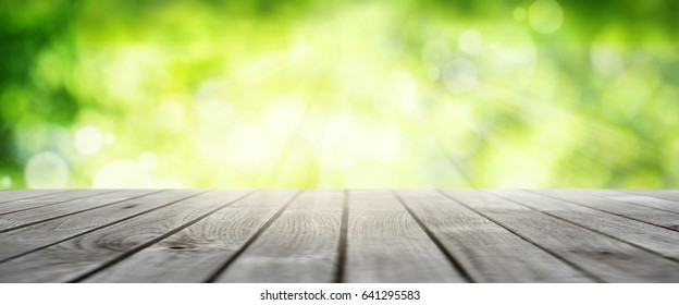 Luminous green spring background with empty wooden floor