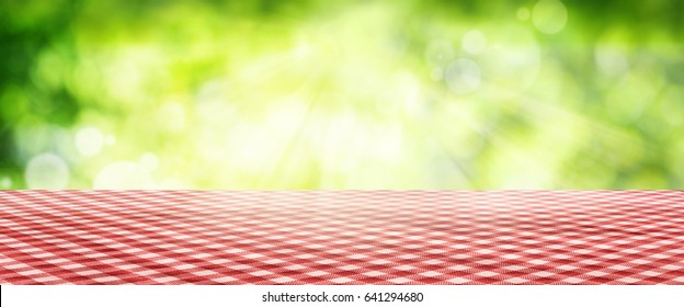 Luminous green spring background with a red checkered Tablecloth for a bavarian concept