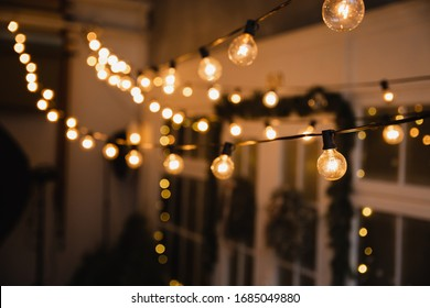 Luminous incandescent lamps hang in the form of a garland on wires, against the background of a shop window. Background from a garland. Incandescent lamps.