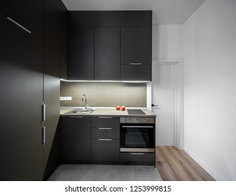 Luminous kitchen with white walls and gray tiles and parquet on the floor. There is a textured tabletop with a sink and garnets, stove, oven, dark lockers and drawers, door. Horizontal.