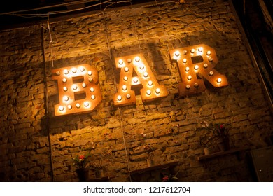 Luminous letters BAR. Volumetric letters BAR from rusty metal on a brick wall with a garland of incandescent lamps. BAR signboard. Inscription BAR from large metal letters decorated with glowing light