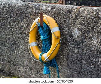 A luminous life saving ring and buoyancy hangs on the harbor wall in Ballintoy on the North Coast of Ireland