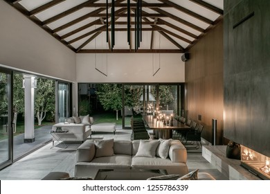 Luminous modern hall with white and wooden walls, large windows with glass doors, beams on a ceiling and a tiled floor. There is a burning fireplace, sofas with pillows, tables with wicker chairs.