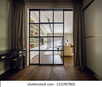 Luminous modern interior with a glass sliding door, light walls and a parquet with a carpet on the floor. There are different tables, sofas, lockers and shelves with books, TV, lamps, curtains.
