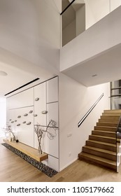 Luminous modern interior with white walls and a stair with wooden rungs and a glass railing. There is a wall decorated with chrome birds, wooden rack with glass vases with plants and light candles.