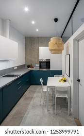 Luminous modern kitchen with white and concrete walls, gray tiled floor. There are blue lockers and drawers, table with lemons, chairs, hanging wicker lamp, stove, oven, tabletop with bread and plant.