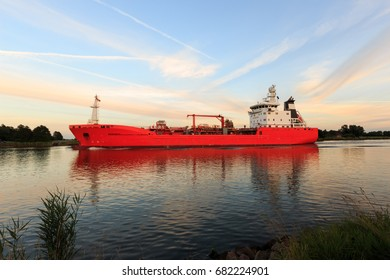 Luminous orange bulk carrier on North Sea and Baltic canal on a sunny afternoon