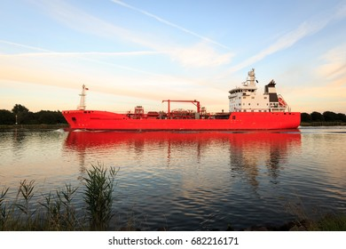Luminous orange bulk carrier with reflections on North Sea and Baltic canal on a sunny afternoon