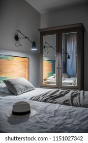 Luminous room in a hotel with light walls. There are two beds with a colorful wooden bedhead, black lamps on the wall, window with curtains, nightstand, dark gray wardrobe with mirrors. Vertical.