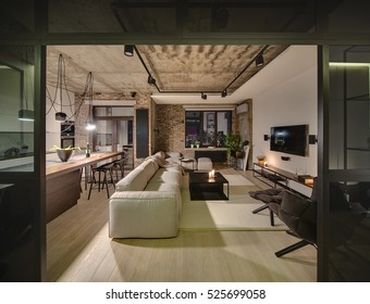 Luminous sitting-room in a loft style with different walls and a concrete ceiling. There are light sofas, wooden tables, different chairs, armchair, TV, lamps, kitchen zone with kitchen equipment.