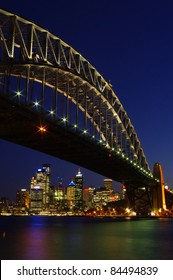 Luminous Sydney Harbor Bridge at night with colorful lighting and the skyline of the city center in vertical frame