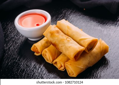 lumpias with sweet sauce on a black background