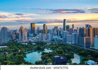 Lumpini Park and Bangkok city with colorful sky in sunset time. ( With flare of warm sunlight effect create reflection at the building and blur advertisement trademark, brand, logo.)