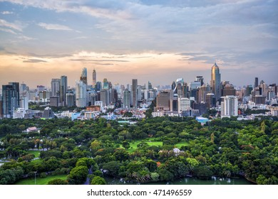 Lumpini Park and Bangkok city in sunset time. ( With warm sunlight effect create reflection at the building and blur advertisement.)