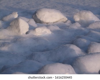 Lumps of snow in the rays of sunset. Close-up. Snow background.