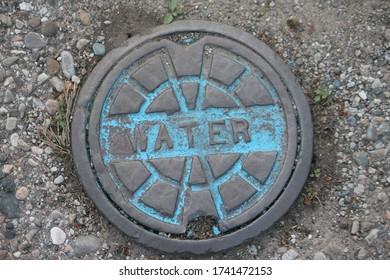 LUNA PIER, MICHIGAN/U.S.A.: MAY 24, 2020 : A local water utility line manhole cover in the small town of Luna Pier, Michigan.