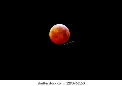 Lunar eclips, also known as a blood moon, with contrails in front of it on January 21, 2019 in The Netherlands