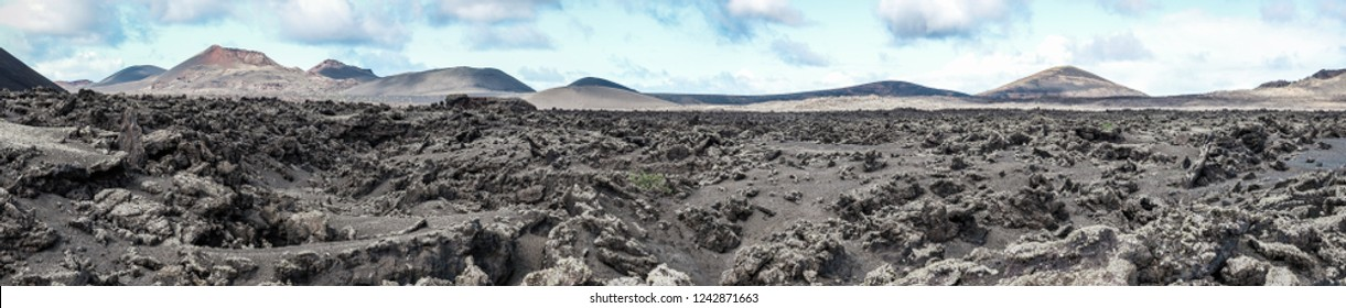 Lunar landscape. Lava field with volcanoes and caldera in the background. Lanzarote, Canary Islands. Panorama