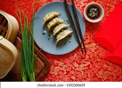 Lunar New Year lucky food steamed Chinese dumplings served on red fabric background with chopsticks, red envelope, bamboo basket, soy sauce mixture. A traditional dish eaten on Chinese New Year's Eve.