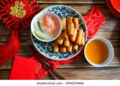 Lunar New Year Lucky food deep fried spring roll on wooden background with red hanging with Chinese blessing word means 'good fortune', red fabric, red envelope, white bowls with dipping sauce.