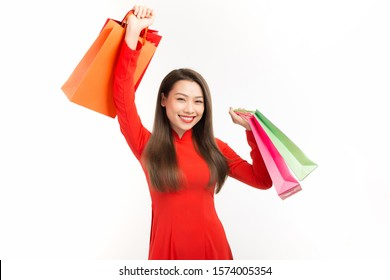 Lunar new year woman concept, Asian woman wear red dress holding shopping bags on white background