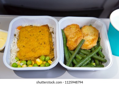 Lunch in the aircraft. In-flight food. Hot dish in the aluminum lunch boxes: fish, chicken, rice, kidney beans, peas, corn.