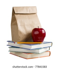 Lunch bag with apple and pencil on top of books.