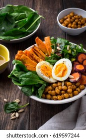 Lunch bowl with sweet potatoes, chickpeas, spinach, carrots and boiled egg