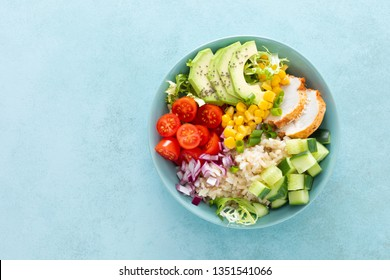 Lunch bowls with grilled cgicken meat, rice and fresh salad of avocado, cucumbers, corn, tomato and onion