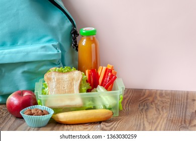 Lunch box with appetizing food and apple, juce, backpack on wooden table