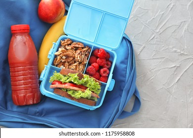 Lunch box with appetizing food and bottle of juice on bag