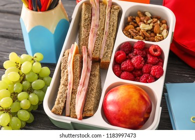 Lunch box with appetizing food on wooden table