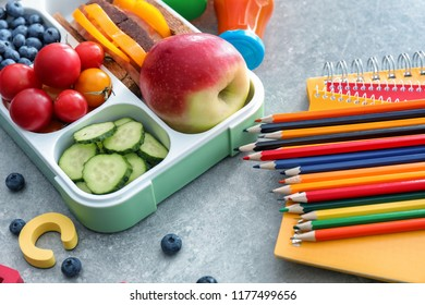 Lunch box with appetizing food and stationery on grey table