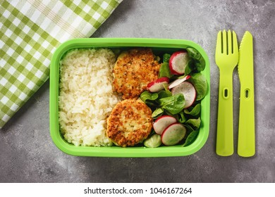 Lunch box with boiled rice, chicken cutlets ans radush salad.